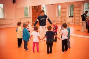Zajęcia, treningi dla dzieci, 8 dzieci i instruktor trzymają się za ręce stojąc w kole.